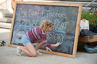 Linnea Propp-Pearson '17 writes on a chalk board. Occidental College students march in a rally organized by Fossil Free Occidental on Nov. 14, 2014. The group hopes to end Oxy's reliance on fossil fuels by freezing all investments in the 200 largest fossil-fuel companies (measured by their proven carbon reserves in oil, gas or coal) and over the next five to ten years sell the stock in these same companies, and then reinvest 5%, at minimum, of the divested portfolio in socially responsible investments. (Photo by Marc Campos, Occidental College Photographer)