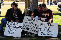 "Phoenix, Arizona. January 19, 2013 - A group of demonstrators hold signs opposing gun control during Saturday's rally in Phoenix. As President Barack Obama proposed new gun regulations last week, gun owners demonstrated against it with national ""Guns Across America"" rallies to defend the Second Amendment. Dozens showed up at the Arizona State Capitol, many of them carrying weapons. Photo by Eduardo Barraza © 2013"