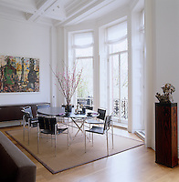 In the dining area, Roquebrune chrome chairs by Eileen Gray surround a Cavalletto table by Luigi Caccia Dominioni