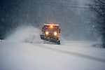 At dusk, heavy duty snowplow clears rural road during a blizzard