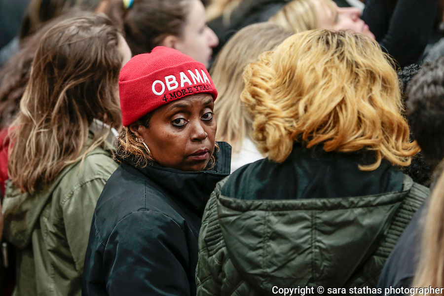 """An African American woman wears an """"Obama 4 More Years"""" knit hat in a crowd."""