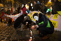 Women of Chinese descent concealed by masks, representing  sex workers in Paris, light candles as they take part in a demonstration on the International Day to End Violence Against Sex Workers at Place Jean Rostand. Chinese sex workers in Paris, who are usually here without legal papers, often experience violence and harassment on the streets from clients and even police. Paris, France. Dec. 17, 2014