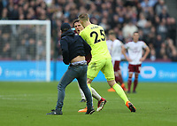 West Ham United's Mark Noble wrestles with a pitch invader as Joe Hart tries to hold him back<br /> <br /> Photographer Rob Newell/CameraSport<br /> <br /> The Premier League - West Ham United v Burnley - Saturday 10th March 2018 - London Stadium - London<br /> <br /> World Copyright &copy; 2018 CameraSport. All rights reserved. 43 Linden Ave. Countesthorpe. Leicester. England. LE8 5PG - Tel: +44 (0) 116 277 4147 - admin@camerasport.com - www.camerasport.com