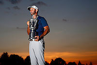 Dustin Johnson holds up the U.S. Open trophy following his first major win in Oakmont, Pennsylvania on Sunday June 19, 2016. (Photo by Jared Wickerham / DKPS)