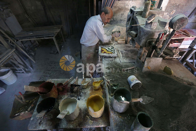 A Palestinian man Hani Rihan, 81, works on a traditional handmade and coloured tiles in the oldest tile factory since 1947, in the West Bank city of Nablus, on September 17, 2019. The Aslan factory in Nablus remains the only one that practice the skill of producing traditional Palestinian tiles in the West Bank. Jalal has been working in the manufacturing of handmade and coloured tiles (Shami tiles) for nearly 50 years practising a traditional craft passed through his family generations and believed to have originated in the Levant. Photo by Shadi Jarar'ah