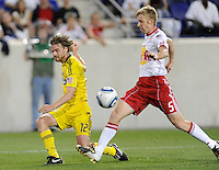 Eddie Gaven (12) of the Columbus Crew crosses the ball past the defense of Tim Ream (5) of the New York Red Bulls. The Columbus Crew defeated the New York Red Bulls 3-1 during a Major League Soccer (MLS) match at Red Bull Arena in Harrison, NJ, on May 20, 2010.