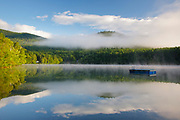 Fog over Mirror Lake in Woodstock, New Hampshire USA on summer morning.