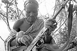 A Turkana man and automatic weapon in a traditional village nr Kakuma, Northern Kenya.<br /> He uses his gun as protection against marauding tribes  that come and steal his livestock.<br /> <br /> With the high amount of unrest in the region there has been a proliferaiton of weapons and a Kalashnikov can be  bought for as little as $10 USD.
