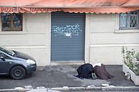 coppia musulmana prega in un posteggio a Como