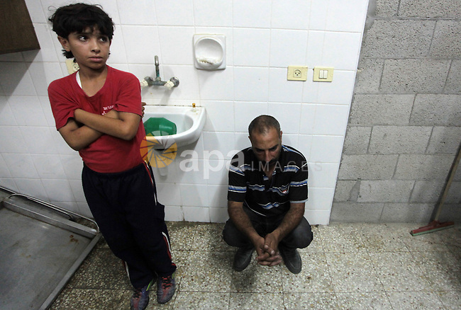 People react after an Israeli air strike killed two Palestinian militants, at a hospital morgue Deir al-Balah in the central Gaza Strip July 6, 2014. Tensions were high along the Gaza border where Israel killed two Palestinian militants and wounded a third in one of about a dozen air strikes in response to rocket fire at southern Israeli towns. Hospital officials confirmed the fatalities, and the Israeli military confirmed it had bombed central Gaza. Photo by Ashraf Amra