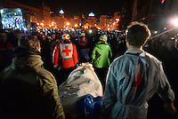 Protesters and red cross volunteers lift and bring a dead body to a makeshift morgue.  Kiev, Ukraine