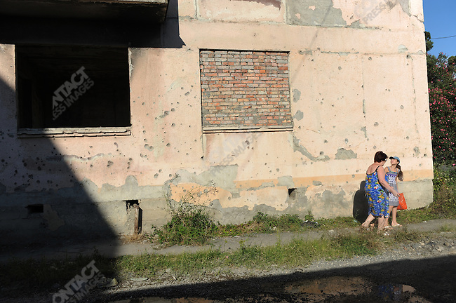On the edge of Sukhumi, the capital of Abkhazia, a woman and children walked through the bullet-marked wall of an apartment building bearing the scars of the separatist conflict with Georgia in 1992-3.  Many of the buildings on the outskirts of Sukhumi remain either unrepaired or abandoned. August 23, 2011