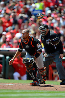 Miami Marlins catcher Miguel Olivo #21 looks for a ball in the dirt in front of umpire Brian O'Nora during a game against the Cincinnati Reds at Great American Ball Park on April 20, 2013 in Cincinnati, Ohio.  Cincinnati defeated Miami 3-2 in 13 innings.  (Mike Janes/Four Seam Images)