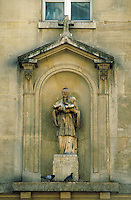 Statue of middle-aged man in clerical robes holding infant. Short pitched roof topped by cross above niche in wall of St. Severin Church. Pigeons forage at base of pedestal. Paris, France.