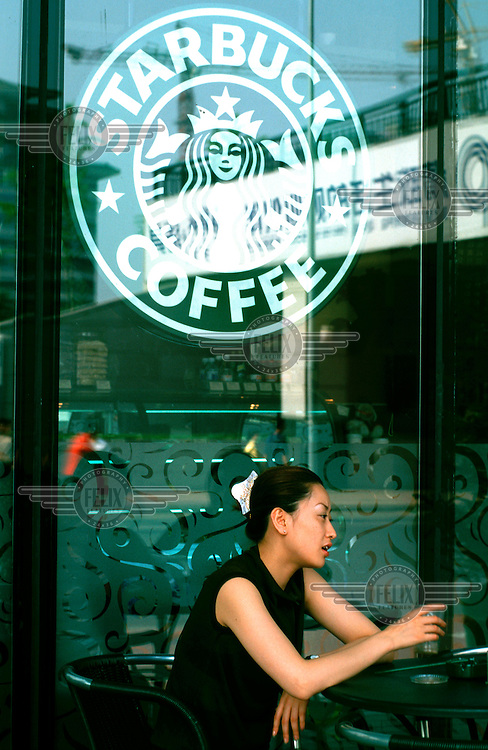 Mark Henley/Panos Pictures..China, Beijing..Young woman on terrace of U.S. Starbucks coffee shop.