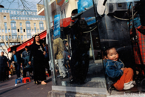France, Paris, 05-2003..Illegal Chinese at phone booths in Paris Belleville district. They are a new wave of immigrants from China?s northeast, home to millions of former cradle-to-grave factory workers laid off by closures. ..