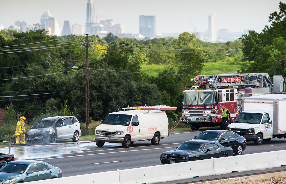 The Austin Fire Department extinguishes a car fire on Texas Loop 1 north MoPac Expressway during afternoon rush-hour traffic with the downtown Austin Skyline in the background.<br /> <br /> Release Information: Editorial Use Only.<br /> Use of this image in advertising or for promotional purposes is prohibited.
