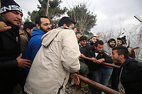 Pictured: Refugees try to bring down the barbed wire gate of the fence Monday 29 February 2016<br /> Re: A crowd of migrants has burst through a barbed-wire fence on the FYRO Macedonia-Greece border using a steel pole as a battering ram.<br /> TV footage showed migrants pushing against the fence at Idomeni, ripping away barbed wire, as FYRO Macedonian police let off tear gas to force them away.<br /> A section of fence was smashed open with the battering ram. It is not clear how many migrants got through.<br /> Many of those trying to reach northern Europe are Syrian and Iraqi refugees.<br /> About 6,500 people are stuck on the Greek side of the border, as FYRO Macedonia is letting very few in. Many have been camping in squalid conditions for a week or more, with little food or medical help.