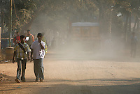 Workers cover their faces up to protect themselves from the dust as they walk to their jobs at an industrial park where Reva Electric Cars is located in Bangalore, India on Thursday, 04 January 2007.