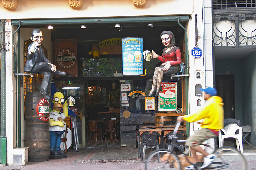 in the San Telmo district around Plaza Dorrego Square, on the square a shop selling flea market things or junk like beer posters and sculptures promoting beer, Homer Simpson, a very busty woman in red and short skirt, a cartoon character, a man in black, a man passing on a bicycle Buenos Aires Argentina, South America