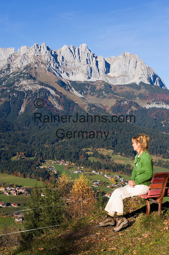 Austria, Tyrol, Kaiserwinkl: autumn foliage and Wilder Kaiser mountains - woman sitting on a bench