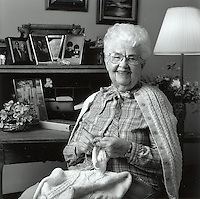 Black and white portrait of female senior citizen, knitting in environment.