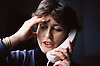 Woman talking on telephone looking thoughtful,