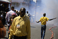 A security guards advises to curios people to stay away from coming explosion of tens of meters long firecrackers in the city.....End of year 2010 celebrations on the streets of Paramaribo. Suriname is one of biggest consumer in South America that using firecrackers, fireworks ( also locally known as pagara ) for celebrations, especially for end of every years and also beginning of every new Chinese Years.