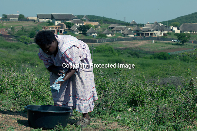 NKANDLA, SOUTH AFRICA - OCTOBER 10: A woman does her laundry outside her one-roomed mud house next to the new home for South Africa president Jacob Zuma's in his birth village on October 10, 2012 in KwaNxamalala, Nkandla. South Africa.  The South African government is spending R240-million (about US$ 27 million) to construct the vast property for his large family. (Photo by Per-Anders Pettersson)