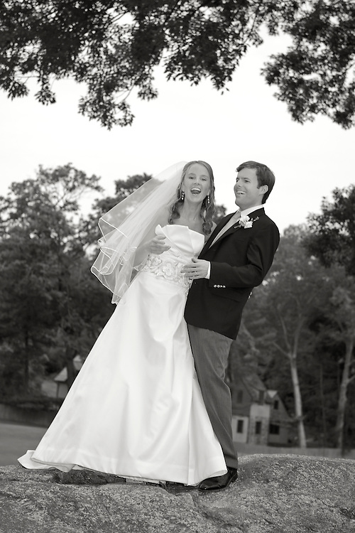 Black & white image of bride and groom standing on top of a boulder.