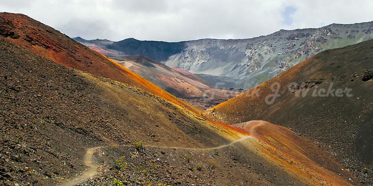 Hiking trail along the orange colored lava sand by the HALALI'I cinder cone in the crater of HALEAKALA NATIONAL PARK on Maui in Hawaii USA
