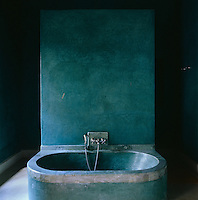 This simple bathroom has been painted a blue/green to match the en-suite bedroom