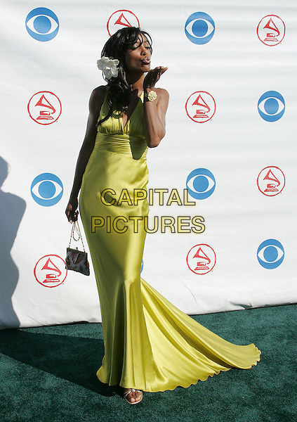 SHAUN ROBINSON.The 5th Annual Latin Grammy Awards held at The Shrine Auditoreum in Los Angeles, California.September 1st, 2004.full length, silk, satin dress, gown, lime green, flower in hair, hair accessory, blowing kiss, gesture.www.capitalpictures.com.sales@capitalpictures.com.Copyright by Debbie VanStory