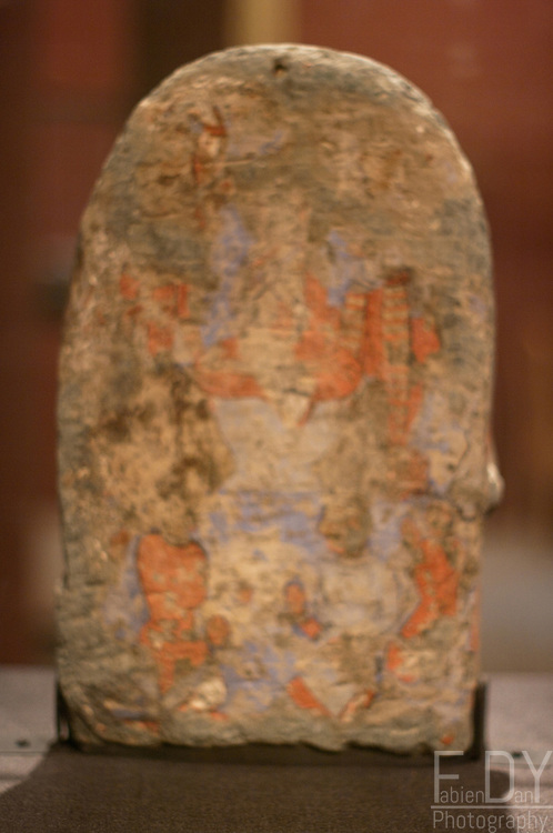Dipankara Buddha. Schist stone painted and gilded, 3rd-5th century AD, found in Mes Aynak (Logar province, Afghanistan). This stele, edged with a row of flames, represents the first part of a story of the previous life of the historical Buddha. Color has been used in statue and then gilded. Paining is visible in the back. Kabul National museum