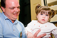 Scott Decker with his daughter Faith poolside at the Share and Care Network's annual retreat held at the Doubletree Guest Suites Hotel in Boston on May 20, 2006. <br /> <br /> The Share and Care Network was created in 1981 by Pat Cahill when her son Scott was diagnosed with Cockayne Syndrome.  A rare form of dwarfism, Cockayne Syndrome is a genetically determined condition whose symptoms include microcephaly, mental retardation, progressive blindness, progressive hearing loss, premature aging, and a shortened lifespan averaging 18 years.  Those afflicted have distinctive facial features, including sunken eyes, pinched faces, and protruding jaws as well as distinctive gregarious, affectionate personalities.<br /> <br /> Because of the rarity of the condition (1/1,000 live births) and its late onset (characteristics usually begin to appear only after one year), many families and physicians are often baffled by children whose health begins to deteriorate after normal development.  It was partly with this in mind that the Share and Care Network was formed, to promote awareness of this disease as well as to provide a support network for those families affected.  In 1998 it began organizing an annual retreat, which has grown from three families in its inaugural year to more than 30 today.  Although the retreat takes place in the United States, families from as far as Japan arrive for this one weekend out of the year to share information and to support one another.