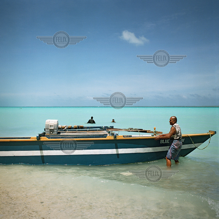 A modern professional design of the traditional Ikiribati fishing boat heads out into the lagoon for reef fishing.