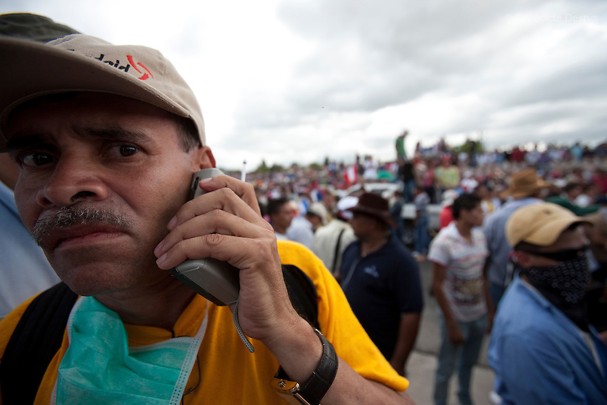 5 July 2009 - Tegucigalpa, Honduras  A supporter of ousted Honduras' President Manuel Zelaya listen to a radio annoucment to know when president arrive while waiting at a border fence of the international airport in Tegucigalpa. Zelaya turned back from an attempted return home on Sunday after soldiers clashed with his supporters as he tried to land, fueling tensions over the coup that toppled him. At least one person was killed and ten were badly wounded when protesters demanding the return of ousted Honduran President Manuel Zelaya clashed with troops at the Tegucigalpa airport. Photo credit: Benedicte Desrus