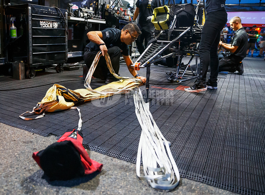 Jul 21, 2017; Morrison, CO, USA; Crew member for NHRA top fuel driver Leah Pritchett packs the parachutes during qualifying for the Mile High Nationals at Bandimere Speedway. Mandatory Credit: Mark J. Rebilas-USA TODAY Sports