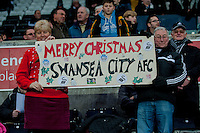 Sunday  14th   December 2014 <br /> Pictured: A man woman hold a Merry Christmas sign <br /> Re: Barclays Premier League Swansea City v Tottenham Hotspur  at the Liberty Stadium, Swansea, Wales,UK