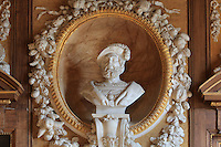 Bust of King Francois I in marble, 1835, by Valois Achille Joseph Etienne, 1785-1862, with gilded frame in carved stucco surrounded by fruit garland, in the Galerie Francois I, begun 1528, the first great gallery in France and the origination of the Renaissance style in France, Chateau de Fontainebleau, France. The Palace of Fontainebleau is one of the largest French royal palaces and was begun in the early 16th century for Francois I. It was listed as a UNESCO World Heritage Site in 1981. Picture by Manuel Cohen