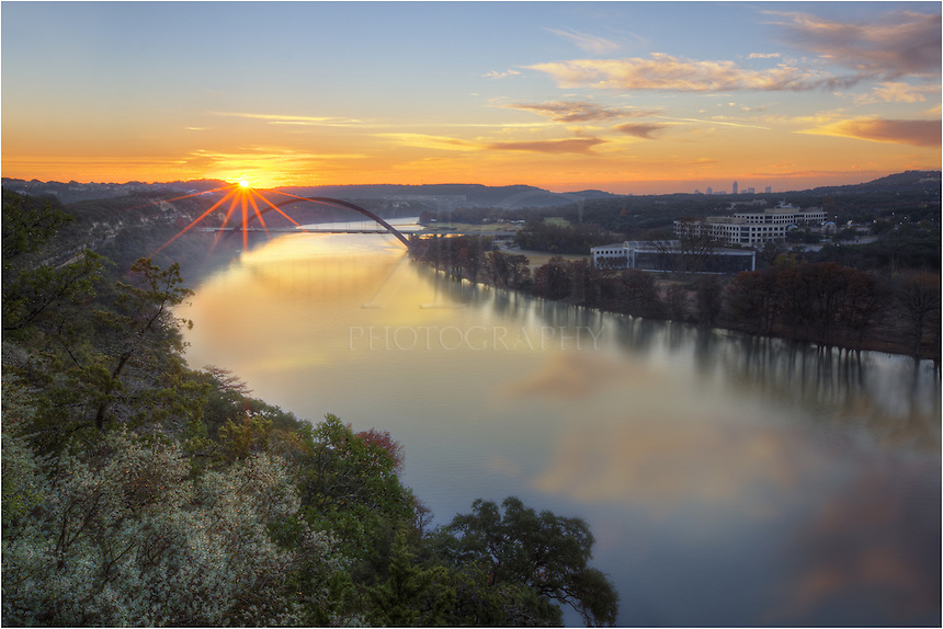 On a cold December morning, the sun rises over Pennybacker Bridge. In this Austin image, you can see the Austin skyline in the distance. There is a short time span when the sun rises so that it shows up in the image. On the Winter solstice, the sun begins tracking back to the north. <br />