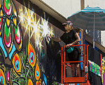 Jenn Ponci paints during the Mural Marathon on Sunday July 1, 2018 in downtown Reno.