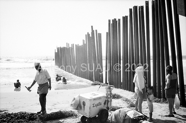 Tijuana, Mexico<br /> August 18, 2007<br /> <br /> The Mexican US border fence dives into the sea on a beach. The beach is split in two by the barrier. The US side is only open to the public on the weekends and people come out to talk with Mexicans through the fence. <br /> <br /> The Mexican beach is always full of life while the US beach is often deserted. Music, children, food, and vendors cover the beach. Mexicans pass back and forth playfully through the barrier under the watchful eye of a border patrolman not far away.<br /> <br /> Signs on the US side warn of the polluted waters that the US says comes from a waste treatment plant on the Mexican side.