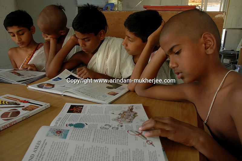 Students of Om Shantidhama during a library session. Om Shantidhama is a residential vedic school for boys. Nestled among the confluence of hills, forest and rivers - Om Shanti Dhama is a world removed from the maddeningly fast and often chaotic urban India. Students from allover the country are selected to take part in its Vedic and free education system. What is unique about this institute is that they have blended the traditional and modern education system. Here computer and science is taught with the same passion as the Vedas and Shastras, helping the students to grow spiritually as well as earn a living. Bonding with the nature and animal world is a mandatory part of the institute's curriculum. Karnataka, India. Arindam Mukherjee