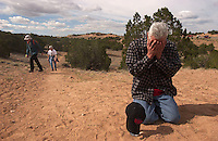 Pilgrim Charles A. Chavez pauses below a roadside cross to pray on his way to the Santuário de Chimayó church, Friday, April 18, 2003. An estimated 10,000 pilgrims walked to the 190-year-old church at Chimayó in honor of Good Friday, a Christian holiday to remember the crucifixion of Jesus. Locals say the earth found in a small room in the back of the church holds miraculous healing powers. Pilgrims have come to the church at Easter for more than 100 years, often traveling the nearly 30 miles from Santa Fe on foot.
