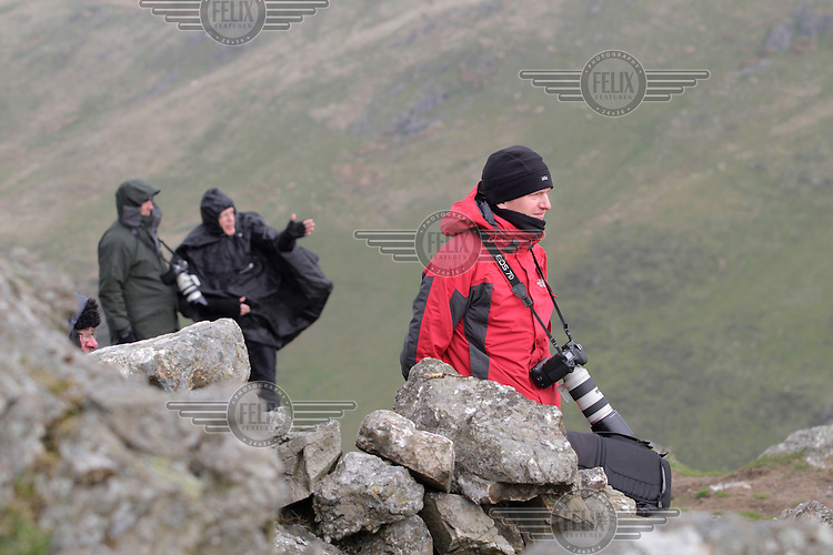 Chris Taylor (red jacket) and other plane spotters at Bwlch wait for airplanes.   The 'Mach Loop' is the nick name of an area in Wales used for low flying by the Royal Air Force. The proximity to the aircraft has made the area popular with plane spotters who come to see and photograph the aircraft.