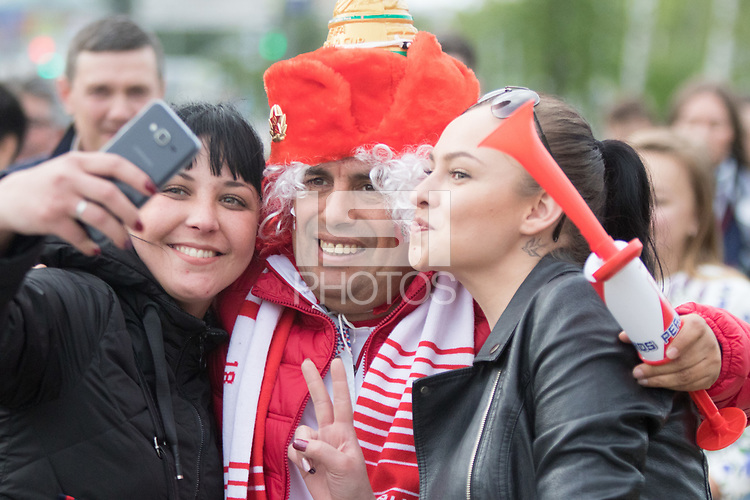 YEKATERINBURG, RUSSIA - June 21, 2018:  Two Russian fans pose for a photo with a Peru fan before the Peru vs. France  2018 FIFA World Cup group stage at Yekaterinburg Arena Stadium.