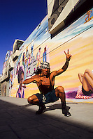 A hispanic tough guy on roller skates in front of wall paintings in Venice LA foto, reise, photograph, image, images, photo,<br />