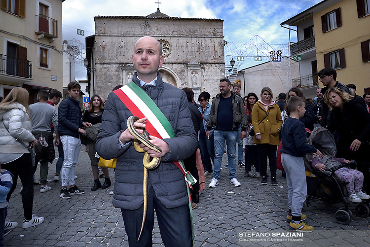 """The Mayor of Cocullo with snakes in hand before the procession.The feast of snakes. Process dedicated to the Saint Dominic, in the streets of Cocullo, in the Abruzzo region, Italy on May 1, 2019.<br /> <br /> <br /> <br /> The St. Domenico's procession in Cocullo, central Italy. Every year on the first  of May, snakes are placed onto the statue of St. Domenico and then the statue is carried in a procession through the town. St. Domenico is believed to be the patron saint for people who have been bitten by snakes:<br /> <br /> Italy, Cocullo, in the Province of L'A...quila, is at 870 meters a.s.l., along the railway line connecting Sulmona to Rome. The village rises alongside Mount Luparo (1327 meters) """"The valley opening in front of the village is surrounded by bare rocks, while on the other side, to the south, snow-capped mountain crests follow one after the other...""""<br /> San Domenico Abate lived in the 10th and 11th centuries AD. Born in Foligno, in the Umbria region, he started his pilgrimages, preaching and ascetic practices in Central Italy, making miracles recorded by the word-of-mouth tradition. He died on 22 January 1031 and was buried in Sora.<br /> <br /> Cocullo snake charmers are over with their snake hunting. They proceeded through the During the procession on the first in May, before the snakes are placed all over the statue of St. Dominick, they will be fed with milk kept in containers with crusca. It is the snake that, most of all other elements, expresses an ancestral myth: the unknown aspect and unpredictability of the natural environment with man's innate need to achieve the dominance on his own habitat. <br /> <br /> Snakes and wolves were the emblems of Italic peoples like the Marsians and Irpinians. Some areas in Abruzzo, especially in the Sagittario valley, were under the menace of wolves and snakes, which for the local populations represented the uncertainty and anxiety of their existence that, together with the precariousness and hardships"""