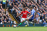 Pictured: Wayne Routledge gets a cross in for Swansea challenged by Gary Cahill<br />